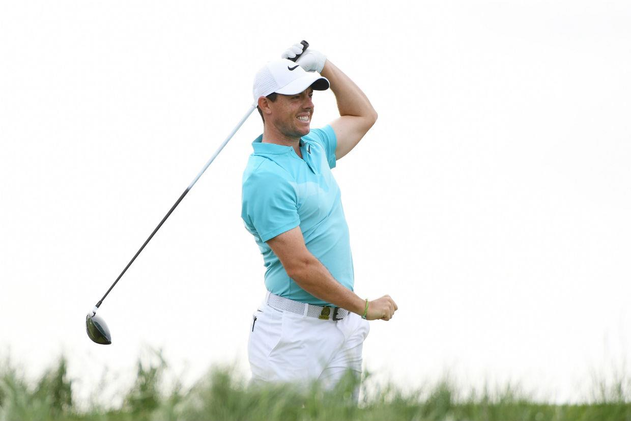 Rory McIlroy grimaces after hitting a wayward tee shot